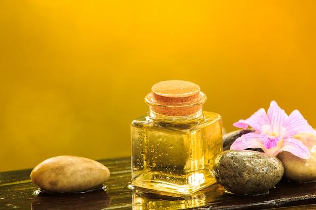 Flasche ätherisches öl oder badekurort des aromas mit zenstein auf holztisch, bild für alternative therapiemedizin des aromabadekurortes und meditationsaromakonzept Premium Fotos