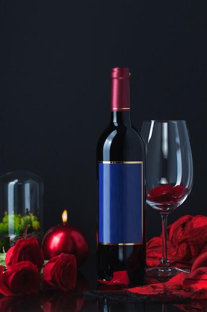 Flasche alkohol mit rosen, becher, kerze und schal Kostenlose Fotos