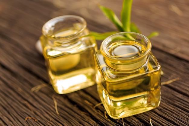 Flasche aromaätherisches öl oder badekurort und natürlicher grüner urlaub auf holztisch Premium Fotos