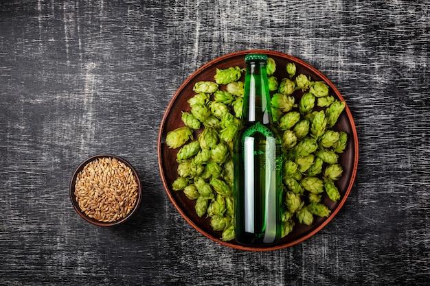 Flasche bier auf einem grünen frischen hopfen in einer platte mit haferkorn vor dem hintergrund einer schwarzen zerkratzten tafel Premium Fotos