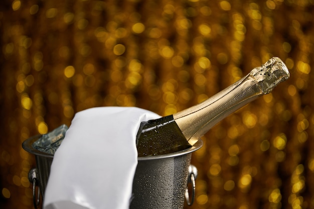 Flasche champagner in einem eimer mit eis auf dem goldenen bokeh Premium Fotos