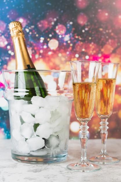 Flasche champagner mit eis und gläsern Kostenlose Fotos