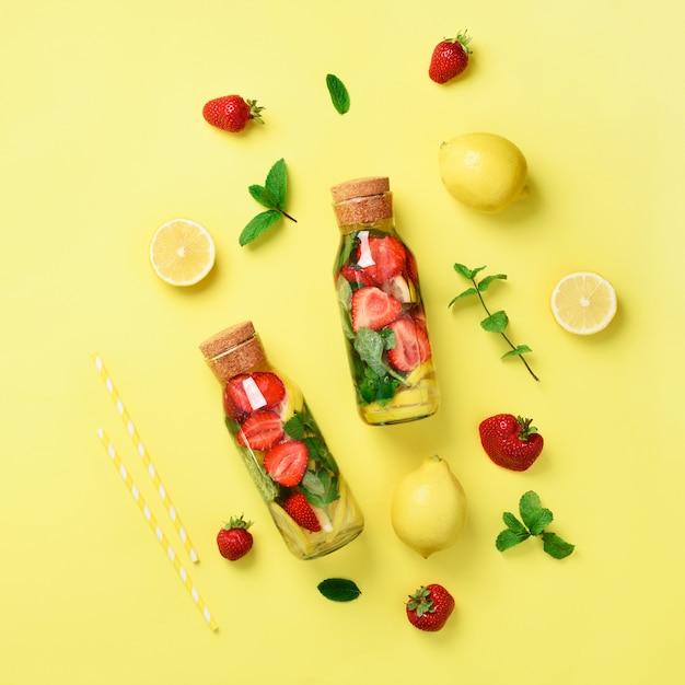 Flasche detoxwasser mit minze, zitrone, erdbeere auf gelbem hintergrund. Premium Fotos