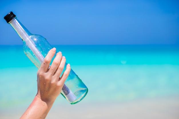 Flasche mit einer nachricht in der hand am blauen himmel Premium Fotos