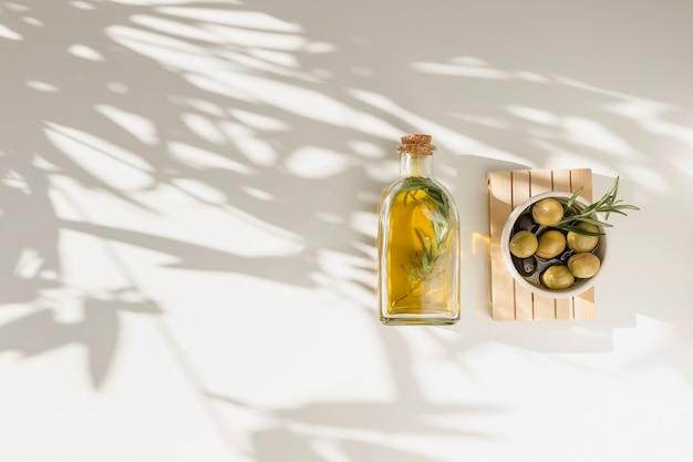 Flasche öl und schüssel oliven auf hölzernem brett über dem weißen hintergrund Kostenlose Fotos