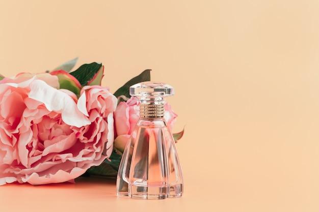 Flasche parfüm mit blumen auf hellem stoff Premium Fotos