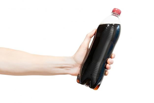 Flasche schwarzes sprudelndes soda in der hand des menschen. Premium Fotos