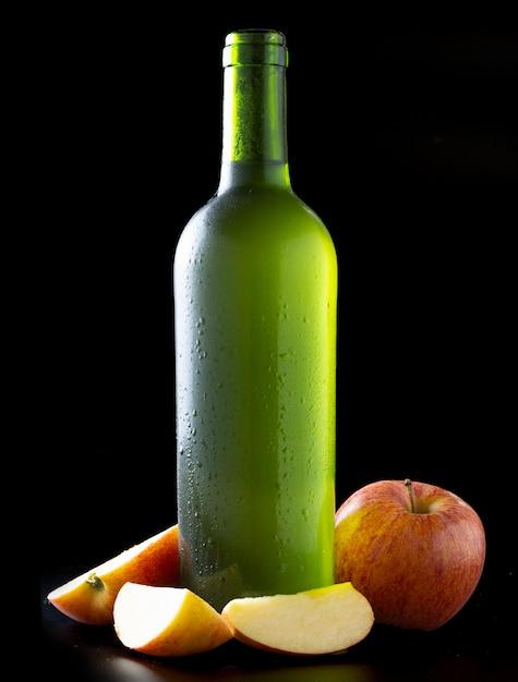 Flasche sehr kalter apfelwein mit äpfeln mit schwarzem hintergrund Premium Fotos