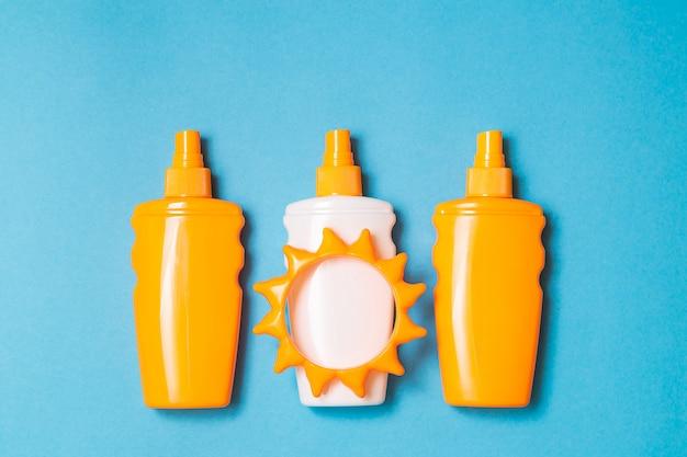 Flasche sonnenschutzcreme oder lotion mit sonnenspielzeugebene legen auf den blauen hintergrund Premium Fotos