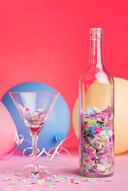 Flasche und glas mit konfetti auf rotem grund Kostenlose Fotos