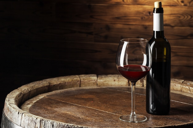 Flasche und glas rotwein auf hölzernem fass schossen mit dunklem hölzernem hintergrund Premium Fotos
