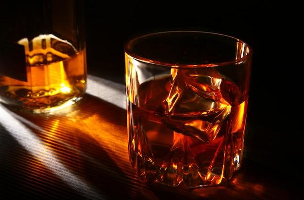 Flasche und glas whisky oder bourbon mit eis auf schwarzer steintabelle. Premium Fotos