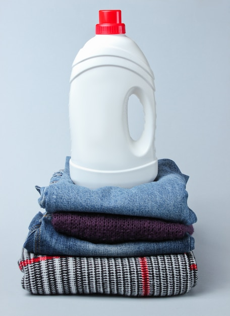 Flasche waschgel auf kleiderstapel auf grauem tisch. Premium Fotos