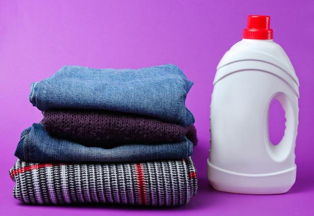 Flasche waschgel auf kleiderstapel auf lila tisch. Premium Fotos