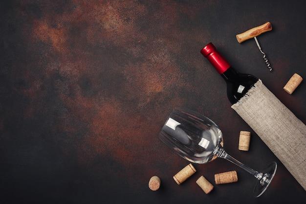 Flasche wein, korkenzieher und korken, auf draufsicht des rostigen hintergrundes Premium Fotos