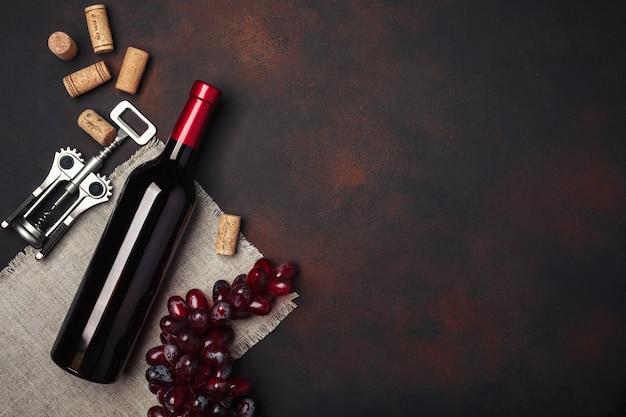 Flasche wein, rote trauben, korkenzieher und korken, auf draufsicht des rostigen hintergrundes Premium Fotos