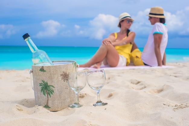 Flasche wein und zwei glückliches paar des glashintergrundes am strand Premium Fotos