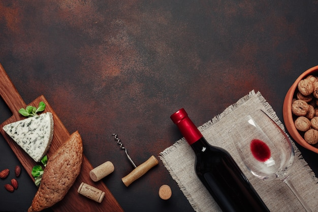 Flasche wein, walnuss, blauschimmelkäse, mandeln, korkenzieher und korken, auf draufsicht des rostigen hintergrundes Premium Fotos