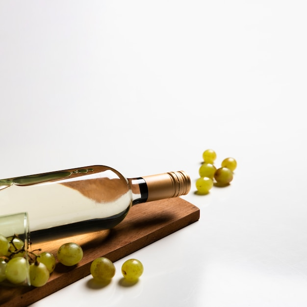 Flasche weißwein auf schneidebrett Kostenlose Fotos