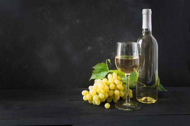 Flasche weißwein mit weinglas, reife traube auf schwarzem holztisch. kopieren sie platz. Premium Fotos