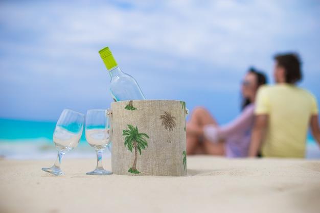 Flasche weißwein und zwei gläser am exotischen sandstrand Premium Fotos
