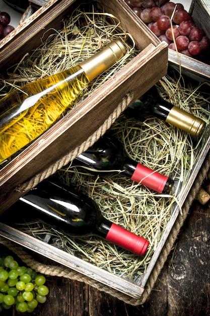 Flaschen rot- und weißwein in alten kisten auf holztisch. Premium Fotos