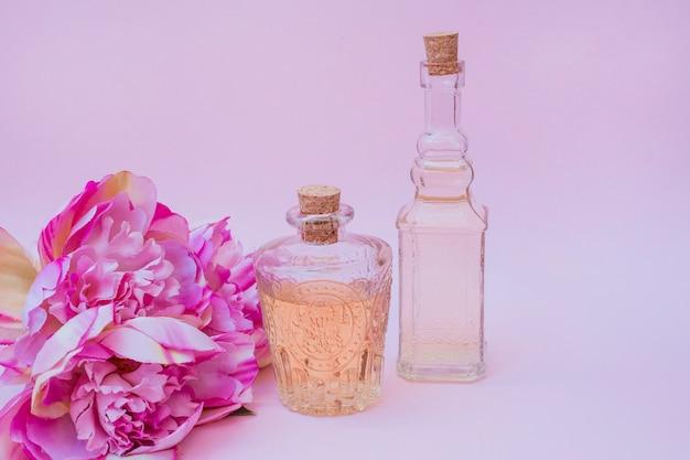 Flaschen und blumen des ätherischen öls auf rosa hintergrund Kostenlose Fotos