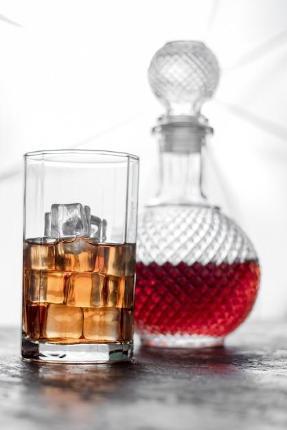 Flaschenwhisky und glas whisky mit eis und licht verwischten hintergrund Premium Fotos