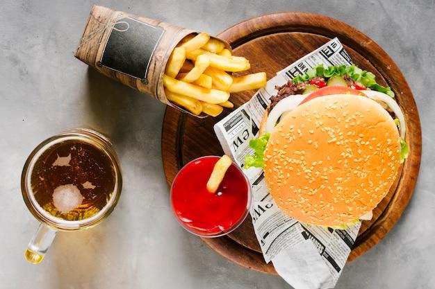 Flat-lay-burger auf holzbrett mit pommes und bier Kostenlose Fotos