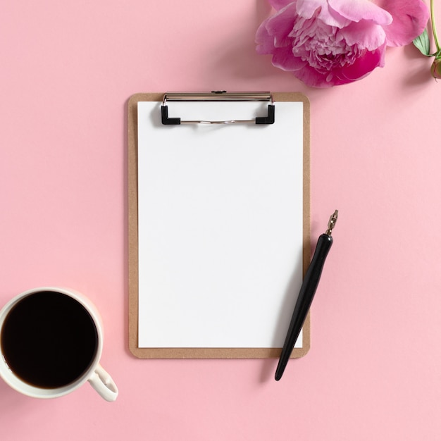 Flatlay des klemmbrettmodells, becher kaffee, kalligraphiestift, pfingstrosenblume auf einem rosa pastellhintergrund Premium Fotos