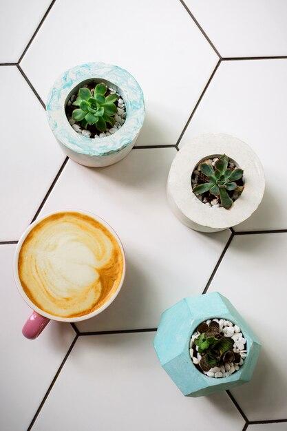 Flatlay mit einer tasse sojalatte in einem rosa becher auf keramiktisch und saftigen blumen in zementtöpfen Premium Fotos
