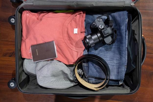 Flatlay von offenem reisekoffer withclothes kamera und pass auf dem hölzernen hintergrund Premium Fotos
