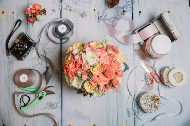 Flatlay von orange hochzeit bouquet und bänder auf arbeitstisch Kostenlose Fotos