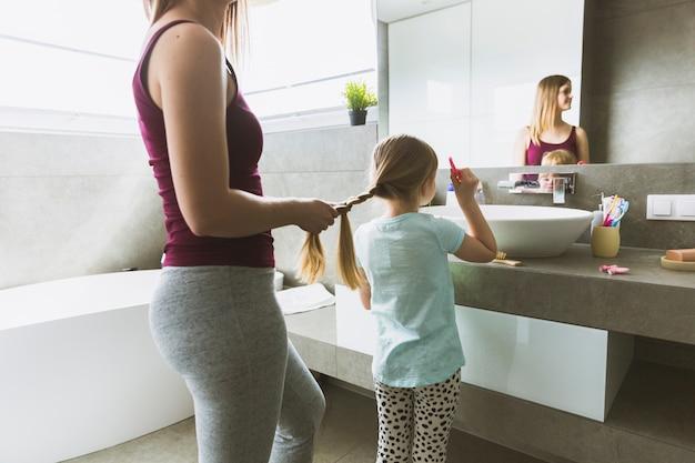 Flechtende tochter der kornmutter im badezimmer Kostenlose Fotos