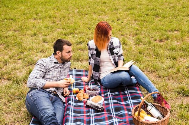 Fleisch fressende banane, die ihr freundinlesebuch am picknick betrachtet Kostenlose Fotos