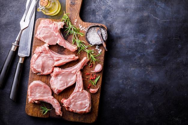 Fleisch-rohes frisches hammelfleisch auf dem knochen würzt chesno rosemary Premium Fotos