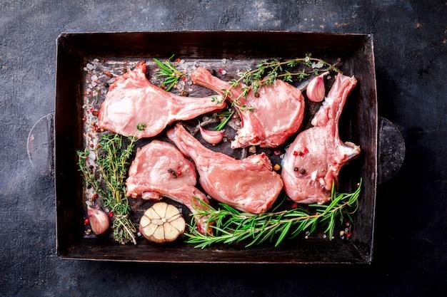 Fleisch rohes frisches hammelfleisch auf den knochen gewürze chesno und rosmarin Premium Fotos