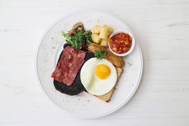 Fleisch steak mit ei, brot, wurst und gemüse Premium Fotos