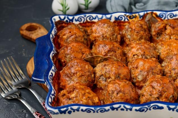 Fleischbällchen in sauerrahm und tomatensauce in keramikform gegen dunkle oberfläche, horizontale ausrichtung Premium Fotos