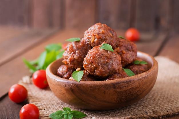 Fleischbällchen in süß-saurer tomatensauce und basilikum in einer holzschale Kostenlose Fotos