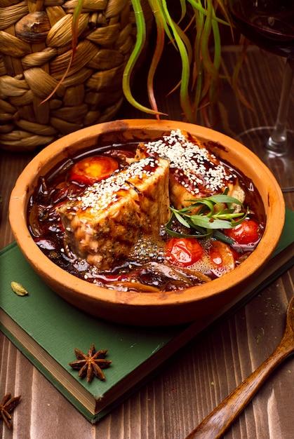 Fleischeintopf mit gemüse, tomaten. gulaschsuppe auf einem buch Kostenlose Fotos