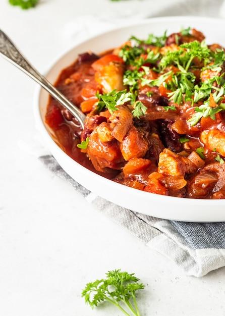 Fleischeintopf mit roten bohnen, paprika und zwiebeln in tomatensauce in einer weißen platte über hellgrauem schiefer Premium Fotos