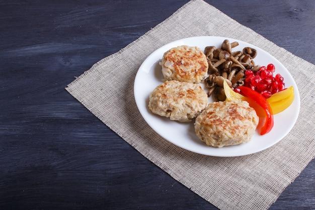 Fleischklöschen mit reispilzen, gemüsepaprikas und granatapfelsamen auf schwarzem hölzernem. Premium Fotos
