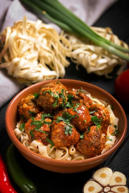 Fleischklöschen mit tomatensauce und teigwaren, nahaufnahme Premium Fotos