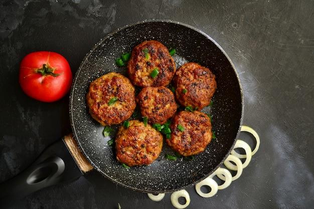 Fleischkoteletts. schnitzel in einer pfanne auf einem schwarzen betontisch. leckeres leckeres essen. draufsicht Premium Fotos