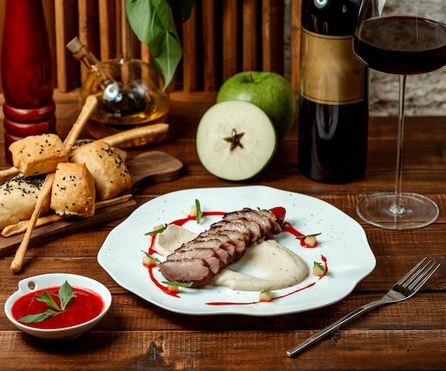 Fleischringe mit apfelmus und einem glas rotwein Kostenlose Fotos