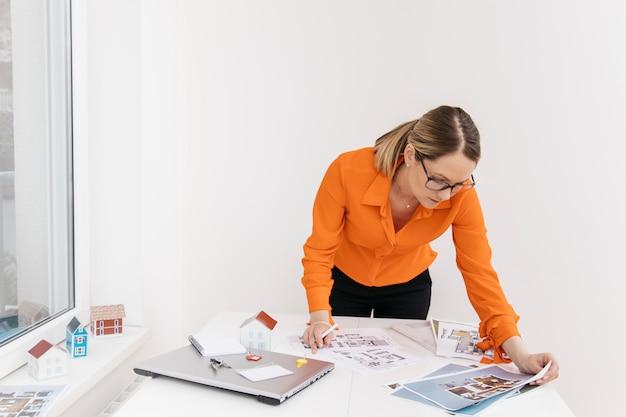 Fleißige frau, die an plan am arbeitsplatz arbeitet Kostenlose Fotos