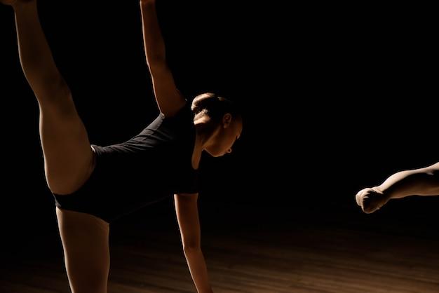 Flexible ballerinas ziehen sich über eine dunkel beleuchtete szene Premium Fotos
