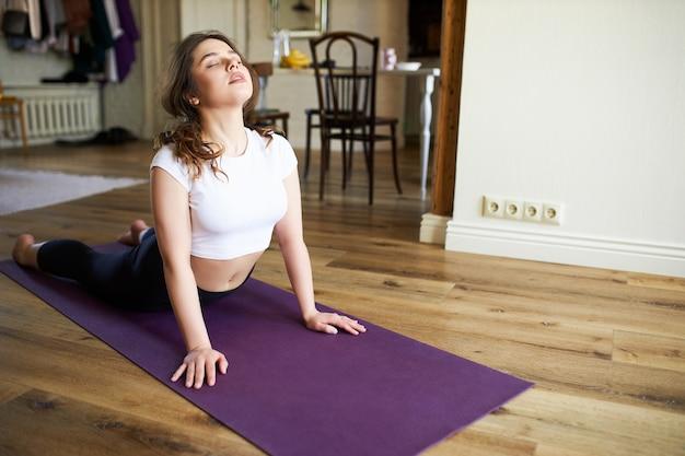 Flexible passform junge frau in sportbekleidung, die morgens sonnengruß-yoga-sequenz übt, sich auf der matte zurückbeugt, nach oben gerichteten hund macht, die augen geschlossen hält und tief atmet. gesunder körper und geist Kostenlose Fotos