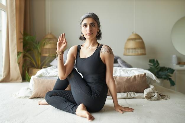 Flexibler junger fortgeschrittener weiblicher yogi mit vorzeitigem grauem haar, der auf dem boden in ardha matsyendrasana-haltung sitzt und sitzende wirbelsäulendrehung tut, um verdauung zu verbessern und rückenschmerzen zu lindern Kostenlose Fotos